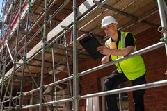 Construction Foreman Builder on Building Site Clipboard and Mug. Male builder foreman, construction worker or architect on site holding a clipboard and drinking stock images
