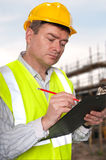 Construction foreman checks clipboard. Foreman on construction site checks details on a clipboard stock photo