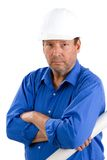 Construction Foreman. Elderly construction foreman wears a hardhat and holds building plans as he works into his retirement years royalty free stock images