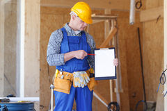 Construction foreman holding a clipboard. Construction foreman wearing a yellow safety helmet holding a clipboard royalty free stock photography