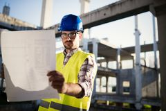 Construction foreman on the job site. With blueprint stock photography