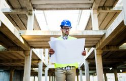 Construction foreman on the job site. With blueprint royalty free stock photography