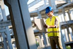 Construction foreman on the job site. With blueprint royalty free stock photo