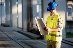 Construction foreman on the job site. With blueprint royalty free stock image
