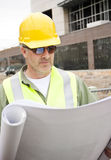 Construction Foreman looking at Blueprints. A handsome construction foreman looking at building blueprints for commercial project royalty free stock photo