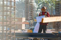Construction Foreman looks over blueprints onsite. Construction Foreman stands in the middle of a construction site, looks over blueprints with rebar in stock image