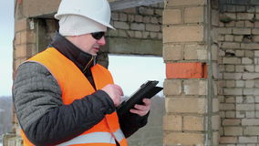 Construction foreman with tablet PC near unfinished building. Winter day stock footage