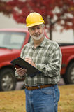 Construction Foreman. Vertical shot of construction foreman holding clipboard and smiling royalty free stock photo