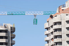 Construction frame on crane between buildings Stock Photography