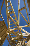 Construction Frame Of An Unfinished House. Low angle view of construction frame of an unfinished house against blue sky stock photo