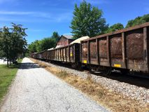 Construction Freight Train Cars with Large Boulders. Rusty freight train cars with graffiti move slowly through Montpelier, Vermont at a railroad crossing by the royalty free stock photography