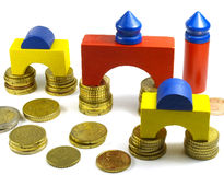 Construction game. Toy wooden pieces and euro coins stock images
