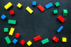 Construction game for kids. Wooden building blocks, toy bricks on black background top view space for text frame. Construction game for kids. Wooden building royalty free stock photography
