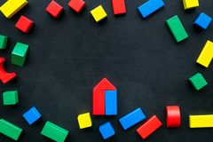 Construction game for kids. Wooden building blocks, toy bricks on black background top view space for text frame. Construction game for kids. Wooden building royalty free stock photos