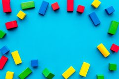 Construction game for kids. Wooden building blocks, toy bricks on blue background top view copy space frame. Construction game for kids. Wooden building blocks stock photos