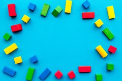 Construction game for kids. Wooden building blocks, toy bricks on blue background top view copy space frame stock image