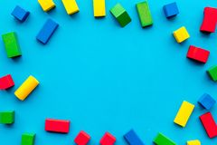 Construction game for kids. Wooden building blocks, toy bricks on blue background top view copy space frame royalty free stock images