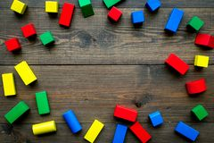 Construction game for kids. Wooden building blocks, toy bricks on dark wooden background top view space for text frame. Construction game for kids. Wooden royalty free stock image