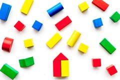 Construction game for kids. Wooden building blocks, toy bricks on white background top view royalty free stock images