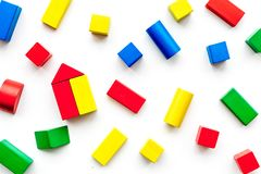 Construction game for kids. Wooden building blocks, toy bricks on white background top view.  stock image