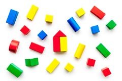 Construction game for kids. Wooden building blocks, toy bricks on white background top view.  royalty free stock photography