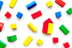 Construction game for kids. Wooden building blocks, toy bricks on white background top view.  royalty free stock images