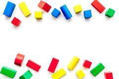 Construction game for kids. Wooden building blocks, toy bricks on white background top view copy space border. Construction game for kids. Wooden building blocks stock photo