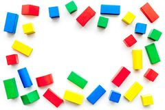 Construction game for kids. Wooden building blocks, toy bricks on white background top view copy space frame. Construction game for kids. Wooden building blocks royalty free stock photography