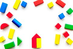 Construction game for kids. Wooden building blocks, toy bricks on white background top view copy space frame royalty free stock photo