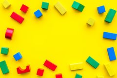 Construction game for kids. Wooden building blocks, toy bricks on yellow background top view space for text frame royalty free stock images