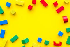 Construction game for kids. Wooden building blocks, toy bricks on yellow background top view space for text frame stock photos