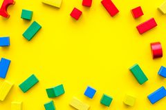 Construction game for kids. Wooden building blocks, toy bricks on yellow background top view space for text frame stock images