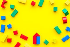 Construction game for kids. Wooden building blocks, toy bricks on yellow background top view space for text frame. Construction game for kids. Wooden building stock photos