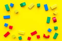 Construction game for kids. Wooden building blocks, toy bricks on yellow background top view space for text frame. Construction game for kids. Wooden building stock images