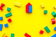 Construction game for kids. Wooden building blocks, toy bricks on yellow background top view space for text frame. Construction game for kids. Wooden building royalty free stock image