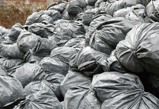 Construction garbage bags in dumpster. Construction garbage bags in metal dumpster royalty free stock photography