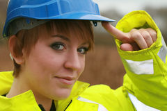 Construction girl. Close up head shot of young woman wearing hard hat and reflective safety jacket and raising her hand to her hat with a cheeky expression stock photography