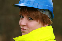 Construction girl. Close up head shot of young woman wearing hard hat and reflective safety jacket stock photos