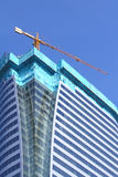 Construction of glass building and crane. The construction of new glass building and crane with blue sky background Stock Photo