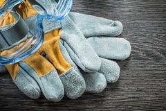 Construction gloves safety spectacles on wooden board Royalty Free Stock Photos