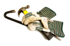 Construction Gloves with Work Tools for Demolition. Construction gloves with crow bar and hammer ready for house demolition work over white Stock Images