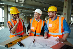 Construction Going Well. Team of cheerful construction workers discussing project details with executive supervisor standing at table with blueprints, tools and Stock Photography