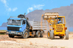 Construction at Graciosa, Canaries. Front end loader loading a truck on a shore of Graciosa; Canary islands, Spain Royalty Free Stock Image