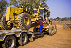 Construction grader on flatbed royalty free stock photo