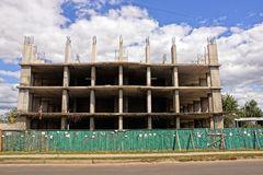 Construction of a gray paneled apartment building behind a fence near the road. Gray concrete frame of a panel house on a construction site behind a wooden green Royalty Free Stock Photography