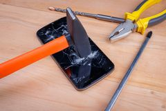 A construction hammer breaks a smartphone, next to it there are flat-nose pliers and screwdrivers. A construction hammer with an orange handle breaks a modern stock images