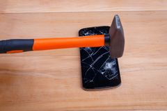 A hammer hits the broken smartphone on the screen. On a wooden background. A construction hammer with an orange punch hits the modern black broken smartphone on royalty free stock photography