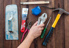 Construction hand tools with hand. Over wooden floor Royalty Free Stock Photos