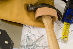 Construction or Handy Man Objects. Supplies of a construction worker or a handy man, including a hammer, tape measure, nails, tool belt and blue prints or plans Royalty Free Stock Photo