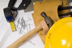 Construction or Handy Man Objects. Supplies of a construction worker or a handy man, including a hammer, tape measure, nails, tool belt and blue prints or plans Stock Images